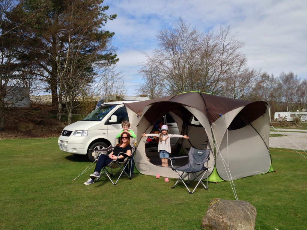 An early photo of the family with the campervan on a campsite
