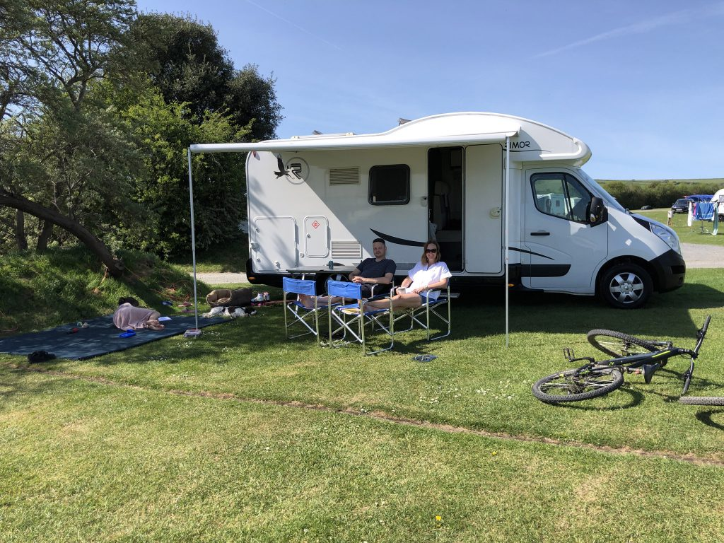 Sitting outside the motorhome on a grassy campsite in North Devon